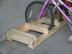 Easy bike rack with scrap wood. why didn't I think of that?  We always have scrap lumber laying around, and my husband refuses to hang bikes (he SAYS it's bad for them. please.)