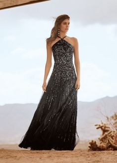 Rendered in 13-yards of sumptuous silk organza, with a floor-sweeping skirt composed of hand-cut bias panels, this St. John custom gown requires a total of 550 hours to complete by hand. Featuring hand-embroidered sequins and beads in a linear pattern sewed on a tulle overlay, this dramatic piece offers evening-ready intrigue.