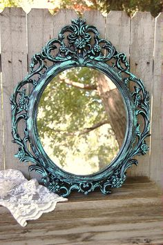 Ornate oval shaped wall mirror hand painted in turquoise blue or light aqua over black, with a protective coating. The mirror has a picture wire hanger. Perfect for wedding, shabby chic, nursery or cottage decor. The mirror is oval shaped, though the photo makes it appear round. 24 tall and 19 wide overall All orders are shipped USPS Priority Mail, Fedex or UPS with insurance and tracking provided.