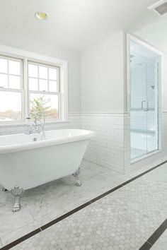 Resplendent long bathroom is fitted with stunning Carrera marble hexagon tiles flanked by dark gray border tiles with staggered marble tiles on either side.