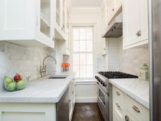White galley kitchen features white cabinets paired with honed white marble countertops and a ...