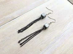 Long dangle earrings with a pyrite cube bead and a variety of chain in silver and black.