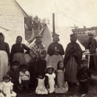 Group of Montagnais in camp: Full-length group portrait of Innu (Montagnais) women and children, standing and seated, some wearing crucifixes, ...