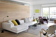 Parketten på gulvet strekker seg oppover langs den ene stueveggen, en morsom og annerledes løsning. Resten av veggene er malt i hvitt. Sammen skaper dette en moderne og enkel base. Noen gule fargeklatter skaper litt liv i rommet.