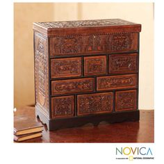 By Julio Sanchez, this jewelry box features a mirror in the lid, eight drawers, and the chest closes with a lock and key. The handcrafted jewelry box emulates colonial traveling chests, and the motifs are taken from pre-Hispanic cultures.