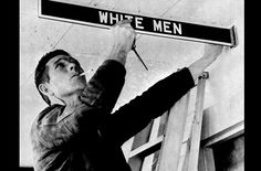 A workman removes a restroom sign at Montgomery Municipal Airport, on January 5, 1962, in compliance with a federal court order banning segregation. However, city officials delayed plans to remove waiting room furniture and close toilets and water fountains. But they said these and the airport restaurant will be closed if there is a concerted integration attempt. (AP Photo) #