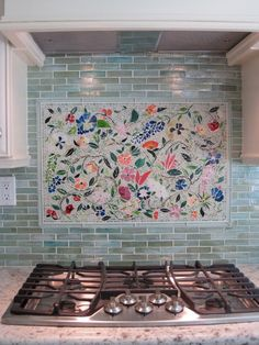 "We created this very custom kitchen backsplash art piece (20"" x 30"") for our client in California. Each tiny tile was hand-cut from sheets of colored stained glass. Our mosaic work was adhered to..."