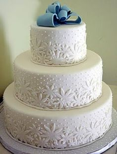 white wedding cake with a pretty blue bow from Paloma of Coco Paloma Desserts