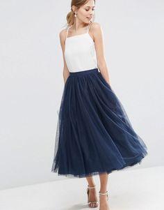 Langer dunkelblauer Tüllrock kombiniert mit schlichtem weißen Top und Riemchen Sandalen in Silber. Das Outfit passt toll zu den blonden Haaren des Models