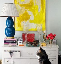 Interior designer Lindsay Harper creates a vignette on her chest of drawers with her collection of jewelry and accessories. A thrift store painting hangs over a vintage chest, illustrating Harper's knack for bargain hunting. Her cat, Coco, makes an appearance.
