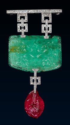 An Art Deco Mughal Cameo Brooch/Pendant, by Strauss, Allard and Meyer, circa 1925. Platinum millegrain brooch/pendant, consisting of a diamond bar from which hang two pairs of open squares, similarly set, supporting an oblong emerald cameo carved with a vase of flowers in front and with a rosette on the back, from which hangs a single open square terminating in a carved ruby drop. #StraussAllardMeyer #ArtDeco #brooch