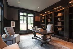 Chic black paneled home office features a black trestle desk and a white and gray trellis fabric upholstered chair stands in front of a wall of floor to ceiling black built in shelves lit by polished nickel picture lamps.