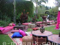 Outdoor Moroccan garden party with Moroccan rugs, low tables, silk floor pillows