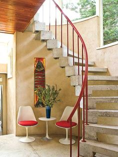 A two-story, screened stair hall adds drama to a formal entry and introduces materials such as concrete and metal.