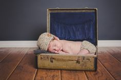 newborn in old suitcase