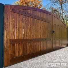 Wooden driveway gate with automatic motors by Dynamic Garage Door. Gorgeous dummy iron hardware, call (714) 451-6349 for a quote! by Dynamic...