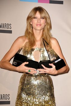 """Taylor Swift poses backstage with the awards for favorite album - country for """"Red"""", favorite female artist - pop/rock, favorite female artist - country, and artist of the year  at the American Music Awards at the Nokia Theatre L.A. Live on Sunday, Nov. 24, 2013, in Los Angeles. (Photo by Jordan Strauss/Invision/AP)"""