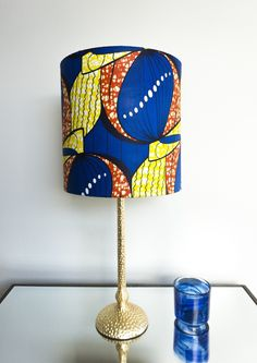 Repin to your own inspiration board.  Fall in love with this handmade royal blue African print lamp shade. The yellow and orange give it a vibrant pop!  Made with a genuine African wax print fabric, 100% cotton. Lampshades are hand-rolled, using a flame retardant PVC hard backing. 12 Inch WASHER TOP wire ring with 1/2 inch recess fitter.