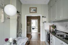 Dit huis zit vol bloemetjesbehang en een mintgroene keuken