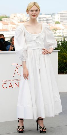 Elle Fanning wore a charming white dress with voluminous sleeves, ribbon detailing, and a ruched bodice. A pair of sky high black and floral embroidered heels finished the look.