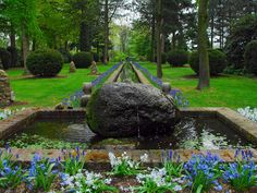 A granite rock fountain bubbles just enough to create movement in this landscaped garden. The soft-blue grape hyacinths and white starflowers add contrast to the boulder and red bricks.