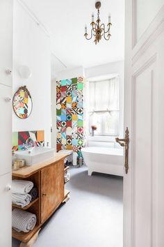 W tym mieszkaniu stare wdzięcznie łączy się z nowym. Obok babcinego kredensu współczesna zabudowa kuchenna, złoty żyrandol i lustro w połączeniu z betonową podłogą i nowoczesną wanną. To mieszkanie zapamiętamy jednak dzięki patchworkowej ścianie – kolaż kolorowych cementowych płytek w łazience to najmocniejszy akcent we wnętrzu.