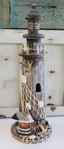 "Nautical wood lighthouse with fishnet, shells, anchor and pelican details stands 14"" high and is a great accent for any coastal themed room."