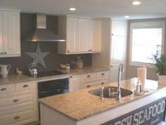 makena's kitchen  taupe gray walls paint color backsplash, white kitchen cabinets, granite countertops, kitchen island and accessories.