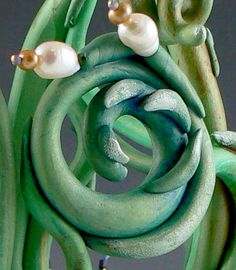 Using pearls, attached with headpins as flower buds.  It's easy and effective.
