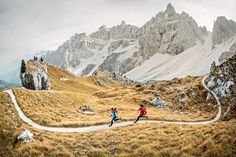 Wide angle photo of two trail runners on perfect single track in the Italian Dolomites
