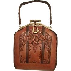 Nicest one of these Art Nouveau tooled leather handbags I have ever seen and in the best condition after a treatment with brown shoe polish.  Tells
