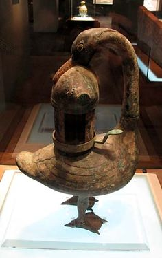 """Side view of an oil lamp, Western Han dynasty, 206 BC - 8 AD, Shanxi Museum. The bronze lamp is shaped like a duck, that holds a fish in its beak. The bird is called a """"goose"""" on the museum label, but geese are vegetarians."""