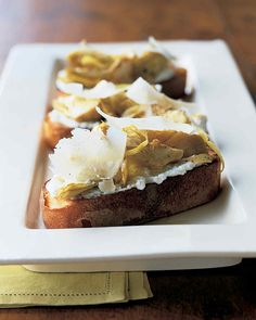 Artichoke hearts with ricotta and Parmesan cheese on hearty slices of rustic bread adds up to a tangy appetizer or finger food that