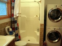 Standing shower with stackable washer/dryer.