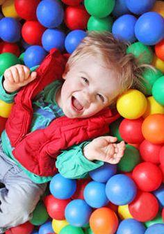 Kid having fun in a ball pit.