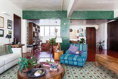 Ladrilho hidráulico com estampa floral e pastilhas verdes nas vigas do apartamento.