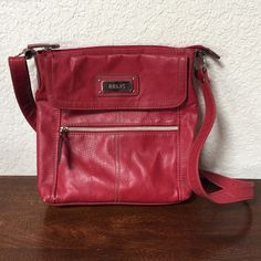 Red Relic Purse Cute cross body Relic in red. There is a little wear on strap and one corner bottom. Otherwise good condition. Price reflects wear. Relic Bags Crossbody Bags