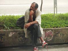Morador de rua sentado na frente do prédio da Gazeta na Av. Paulista