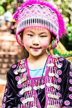 Uma menina da tribo Hmong, em Chiang Mai, na Tailândia, vestindo roupas típicas, nas cores rosa e branco. Ela olha com seus olhos amendoados para a câmera e sorri.