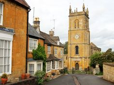 Blockley village in the county of Gloucestershire, England; just another image from the dreamscape world of the Cotswolds. People LIVE on this street can you imagine? Look, there's a castle at the end of my road! Well, how lovely for YOU. At the end of my street there is a great ugly thorn bush and a stop sign.      It's actually a church, but it LOOKS like a castle, doesn't it? IT IS SO BEAUTIFUL!!!**sniffs** This church is circa 1180, constructed in the late Norman style, w
