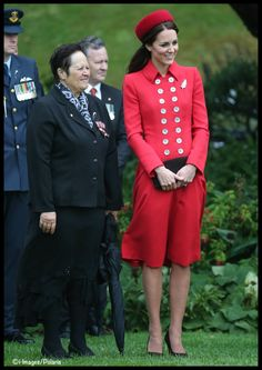 "Catherine, Duchess of Cambridge, aka Kate Middleton, and Maori Elder Hiria Hape, at the official welcome ceremony at Government House, in Wellington, NZ. Kate is wearing the Russian Greatcoat by Catherine Walker, the ""Seaford"" style hat by Gina Foster, brown suede Emmy clutch and heels, and a diamond and platinum brooch in the shape of a fern (a national symbol of New Zealand), on loan from HM the Queen. 4/07/14"
