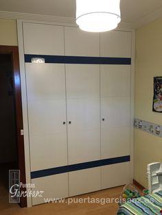 Frente de armarios que hemos instalado recientemente, puertas abatibles ranuradas lacadas en blanco con detalles de cristal en color azul