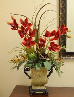 "Red Cymbidium Orchids in Pitcher Planter - Fiery red cymbidium orchids are complemented by soft wisps of grass and feathers, artichoke and lotus pod. Created with high quality faux orchids, displayed in a stately resin vase. This breathtaking design measures 28""H x 17 #silkflowers"