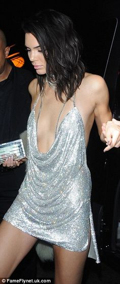 All that glitters... Braless Kendall Jenner risked a wardrobe malfunction in a silver extreme plunging mini as she celebrated her 21st at Catch restaurant in Hollywood on Wednesday