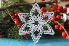 This white paper quilled snowflake ornament is elegant and perfect for hanging on a Christmas tree, making a garland, framing it, or decorating a