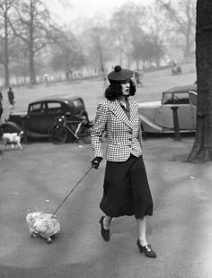 1938 - Accessories clearly reign here — just see: the pom pom beret, fitted blazer, and heeled loafers. And I'm happy to report that cute dogs are still a trend.
