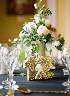 a shimmery gold table number adds a fun sparkle atop a rich black linen. only a few little touches of gold are needed to really bring a theme together.