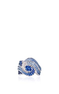 This scintillating ring features round brilliant diamond and lavish blue sapphire embellishments in intricate curvilinear designs.