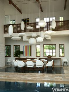 George Nelson Bubble Lights hang at various lengths over a Tucker Robbins table and vintage Saarinen chairs. Decor, Modern Beach House, House, Nelson Bubble Lamp, George Nelson Bubble Lamp, Home Decor, Vintage Chairs, House Interior, Room Decor