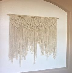 Large, 100% natural cotton macramé wall hanging. Measures approximately 42 in width.  Perfect for hanging above bed.  **Please note-the color of the wall hanging is an off-white, natural unbleached cotton.